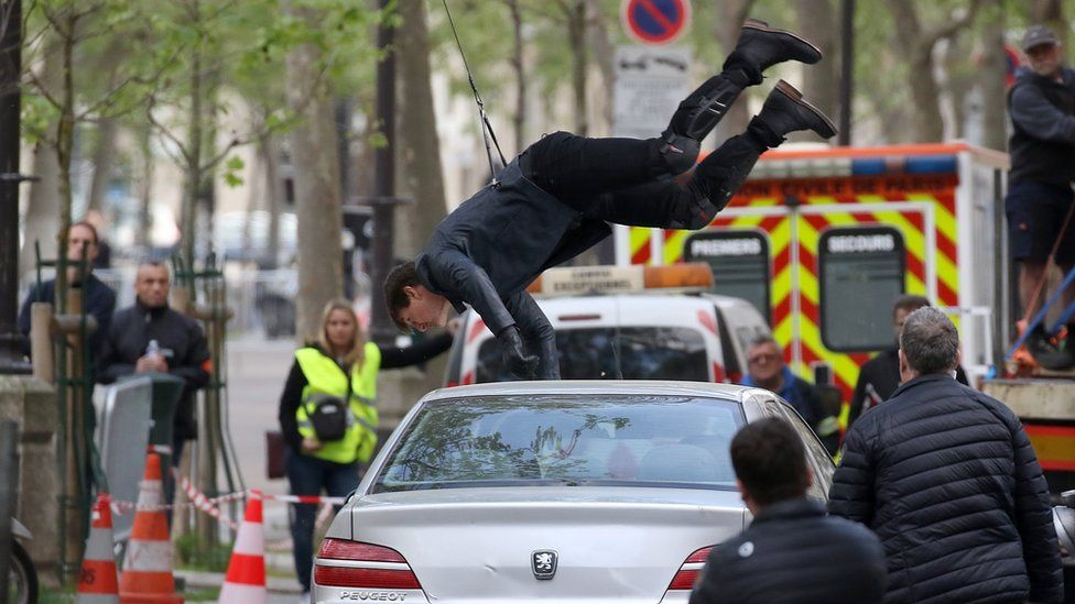 Tom Cruise hanging upside down attached to wires