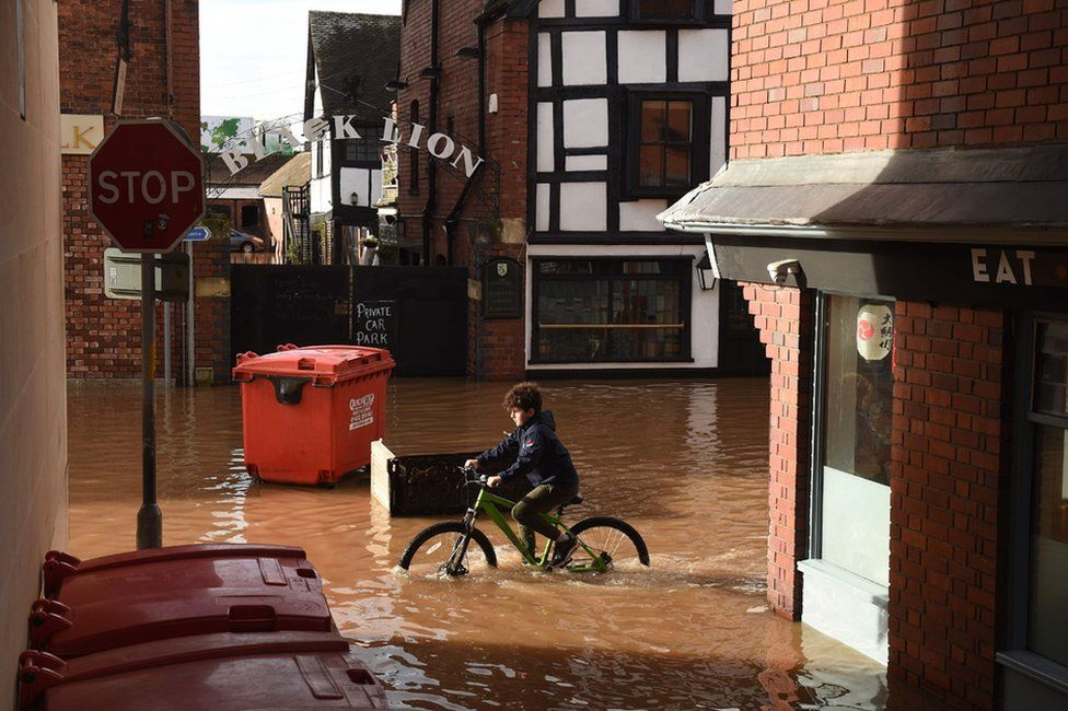 A boy cycles through flood water in Hereford.