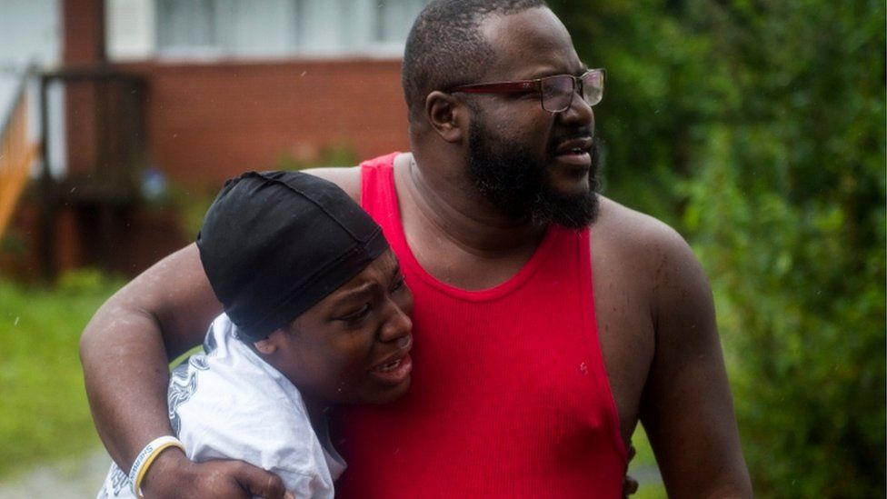 A father and daughter appear emotional as a neighbour is taken away injured from fallen tree