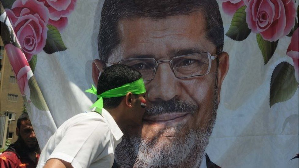 A supporter of Mohammed Morsi kisses his portrait in Cairo (21/06/13)