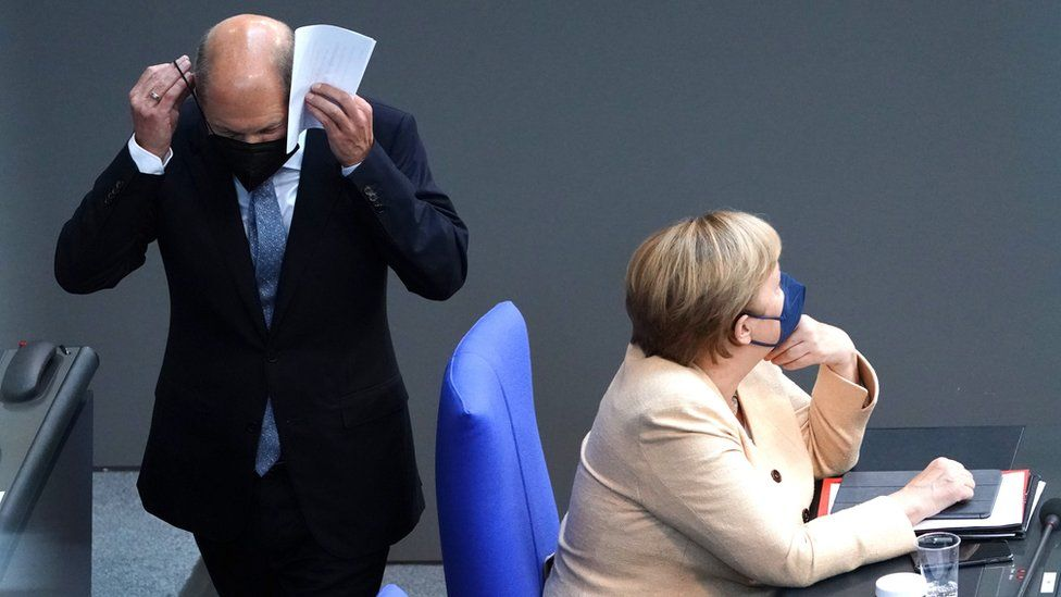 German Minister of Finance and Social Democratic Party (SPD), top candidate for the federal elections Olaf Scholz (L) passes by German Chancellor Angela Merkel