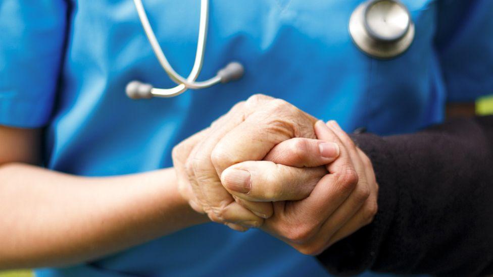 Nurse holding patient's hand
