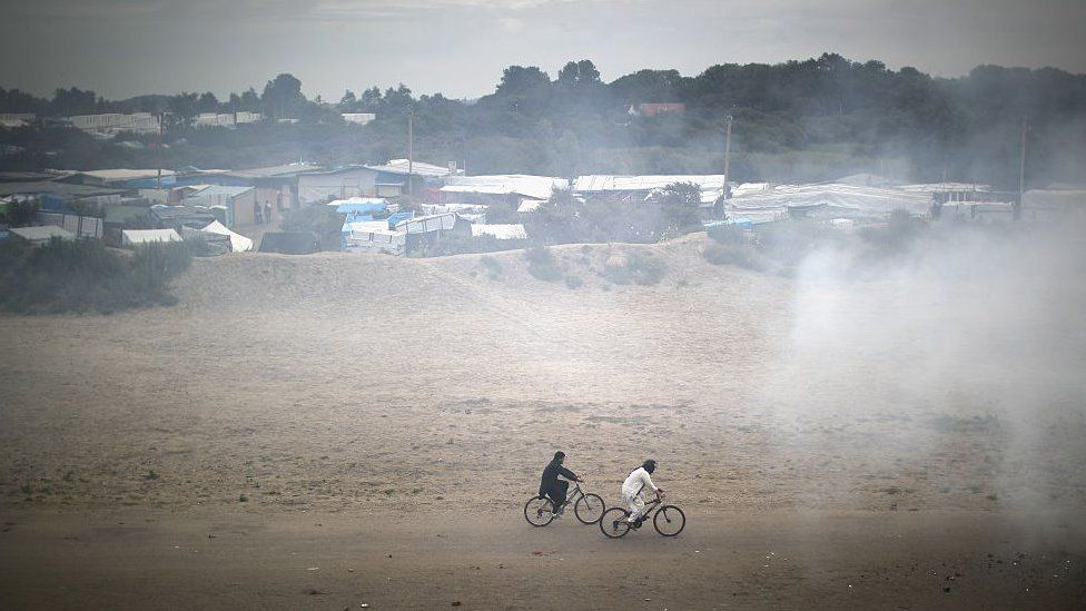 Migrants cycle through smoke from a fire burning rubbish at the Jungle migrant camp on September 6, 2016 in Calais, France.