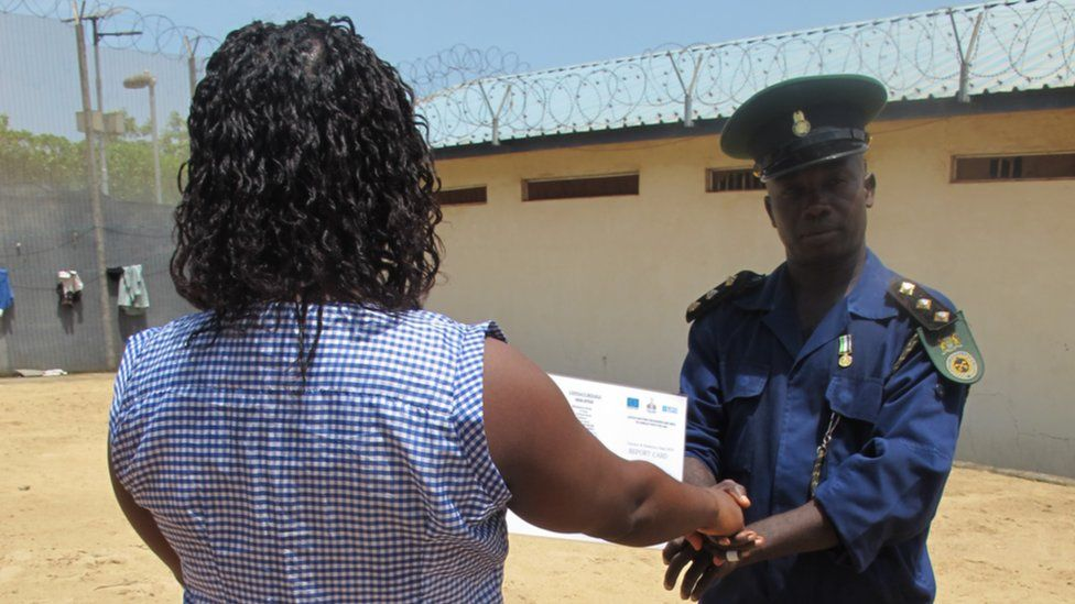 Guard hands certificate to an inmate