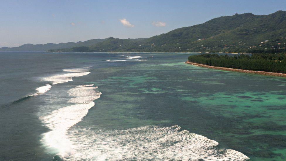 Waves break on the beach of an island in the Seychelles