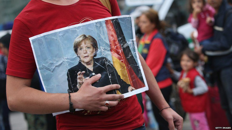 Syrian migrant holds picture of German Chancellor Angela Merkel, 5 September 2015