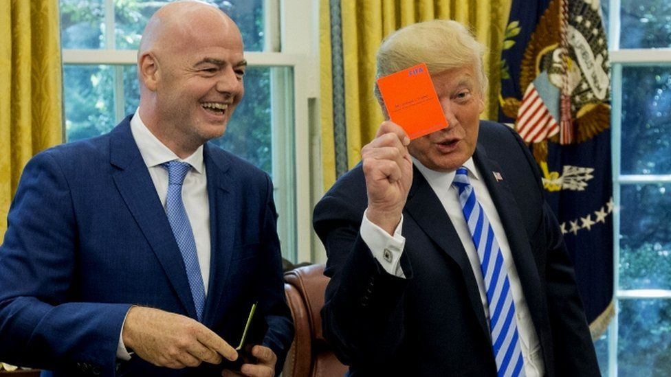 Trump jokingly shows a red card to the media during a meeting with the president of Fifa, Gianni Infantino