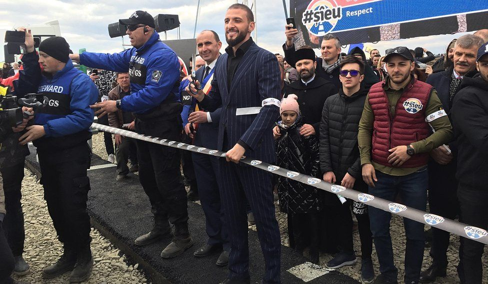 Stefan Mandachi cuts the ribbon across his motorway