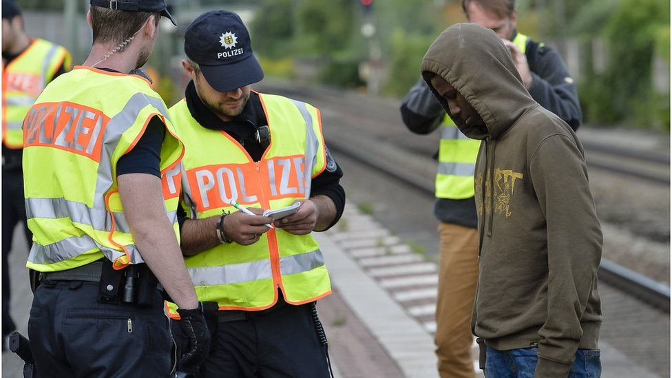 German policemen check a 16 year-old boy from Eritrea after finding him under a train trailer at the train station in the southern German city of Raubling on August 24, 2017