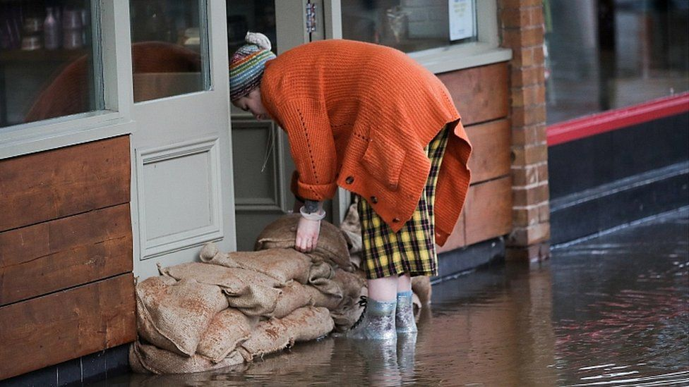 Woman stacking sandbags in Northwich