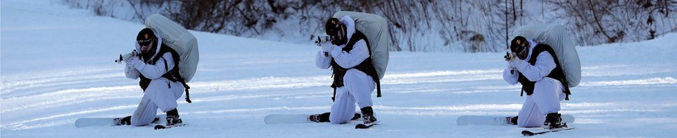 South Korean Marines holding rifles in the snow, while on skis and dressed in white uniforms, in a combined military winter exercise with US Marines in Pyeongchang, South Korea, 24 January 2017.