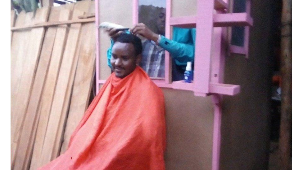 Man getting a haircut with hairdresser behind a wooden shield