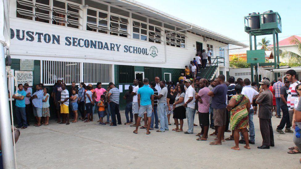 People in Georgetown, Guyana, wait in a queue to cast their vote