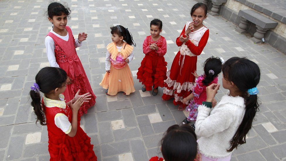 """Yemeni displaced girls, who fled Saada province due to fighting between Shiite Huthi rebels and forces loyal to Yemen""""s exiled President Abedrabbo Mansour Hadi, play on a street in San'aa's old city"""