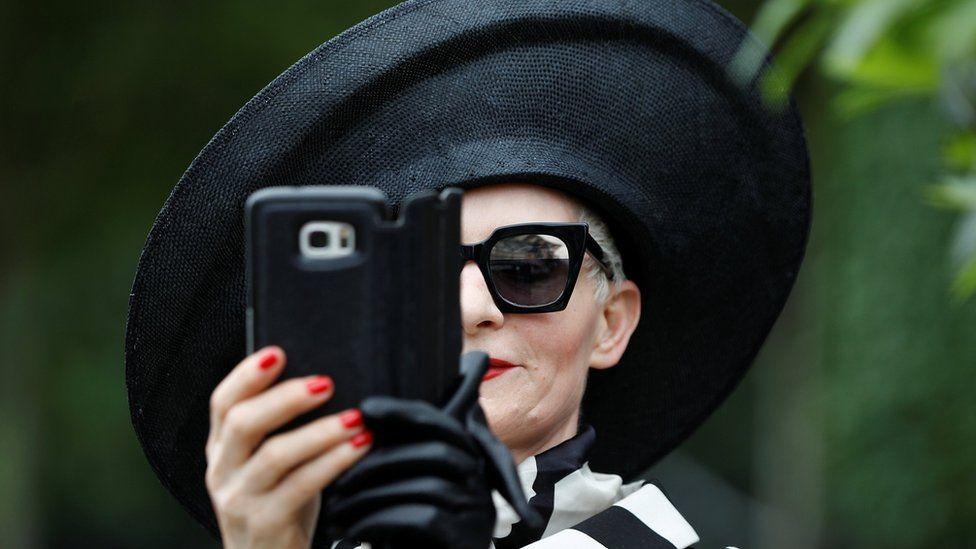 Женщина в шляпе делает селфи