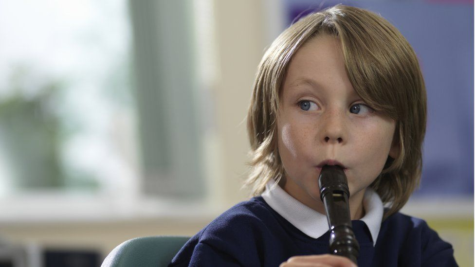 little boy plays recorder