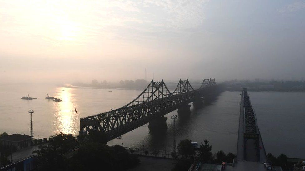 The North Korean town of Sinuiju (at rear) is seen behind the Friendship Bridge (L) which connects Sinuiju and the the Chinese border city of Dandon