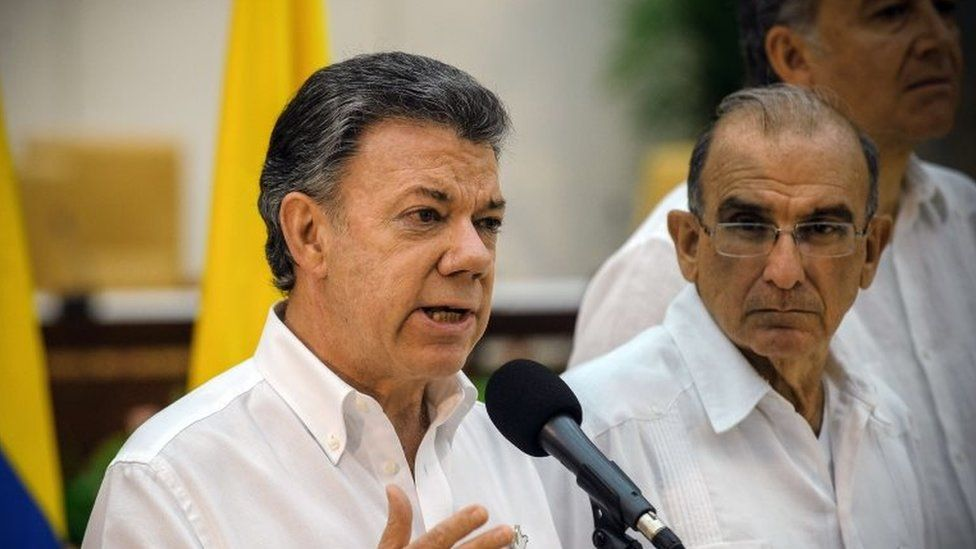 Colombian President Juan Manuel Santos speaks next to the head of the Colombian government delegation for the peace talks during a press conference in Havana on 23 September 2015