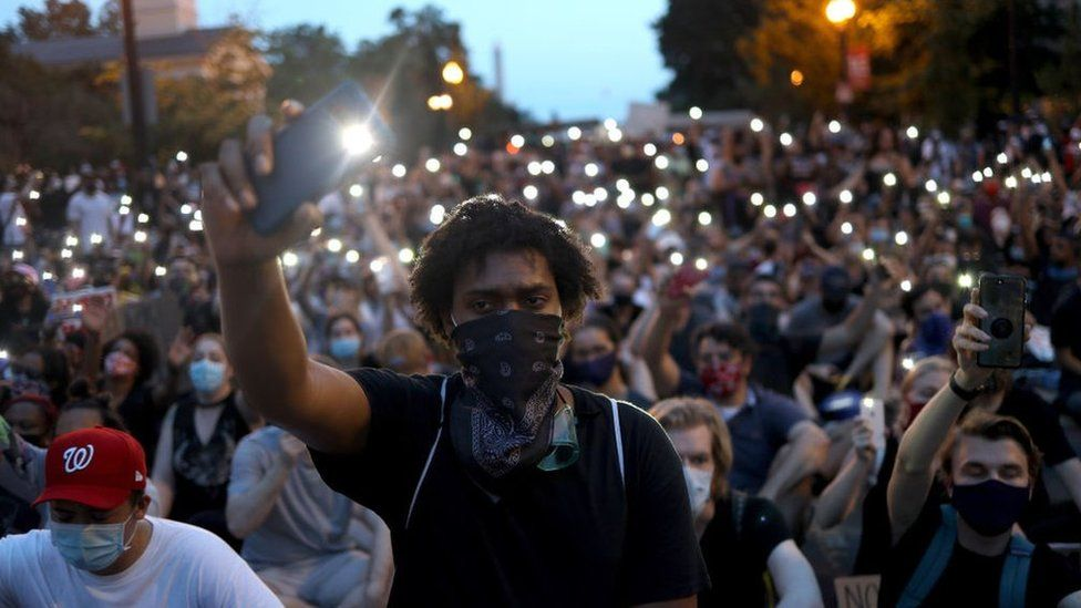 """Demonstrators sing """"Lean On Me"""" near the White House during a peaceful protest against police brutality and the death of George Floyd, on June 3, 2020 in Washington, DC"""