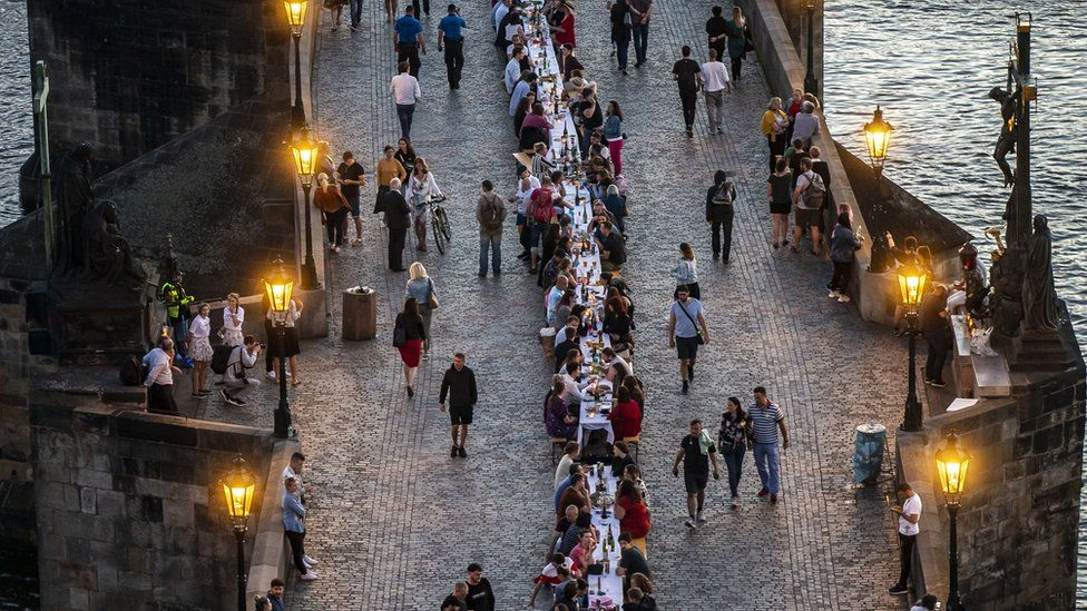 People sit at a long table on the Charles Bridge