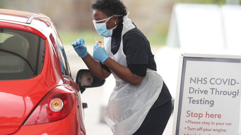 A nurse takes a swab at a Covid-19 Drive-Through testing station for NHS staff on March 30, 2020 in Chessington, United Kingdom