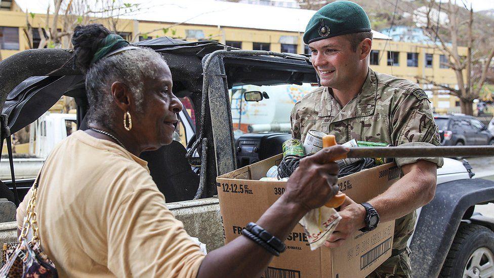 UK soldier giving citizen supplies before Hurricane Maria hits BVI