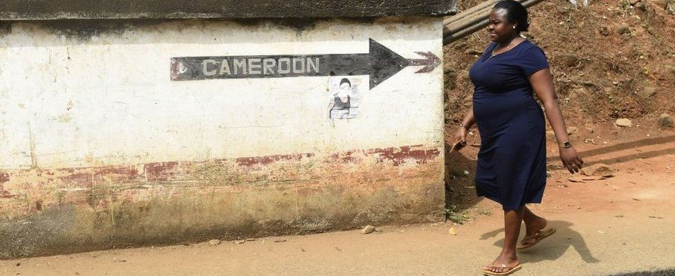 A woman walks into Nigeria from Cameroon at a checkpoint border between Cameroon and Nigeria, in Mfum, in Cross Rivers State