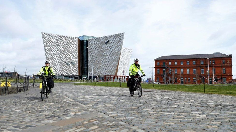 Police officers on bikes are seen in front of the Titanic Belfast Museum in Belfast Harbour, as the spread of the coronavirus disease continues