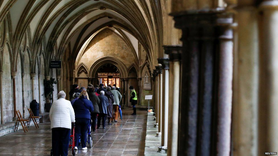 Elderly people queuing for a vaccine in the cloisters of Salisbury cathedral