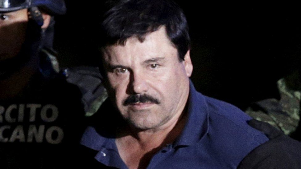 """Recaptured drug lord Joaquin """"El Chapo"""" Guzman is escorted by soldiers at the hangar belonging to the office of the Attorney General in Mexico City, Mexico January 8, 2016. REUTERS"""