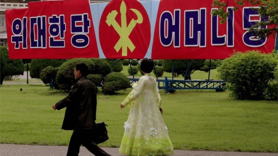 "North Koreans walk past a slogan which reads ""Great Party, Mother Party"" along a sidewalk Wednesday, May 4, 2016, in Pyongyang, North Korea."