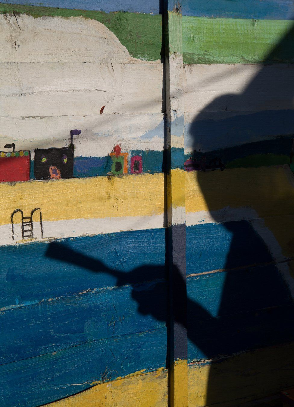 The shadow of a man paints a fence