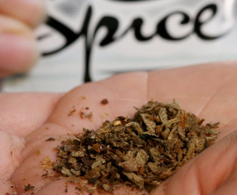 """A young woman holds up a bag of """"Spice"""""""