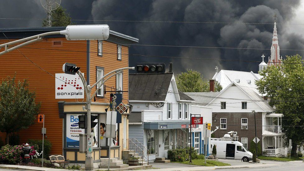 A cloud of smoke is seen over Lac Megantic after a train explosion, 6 July 2013