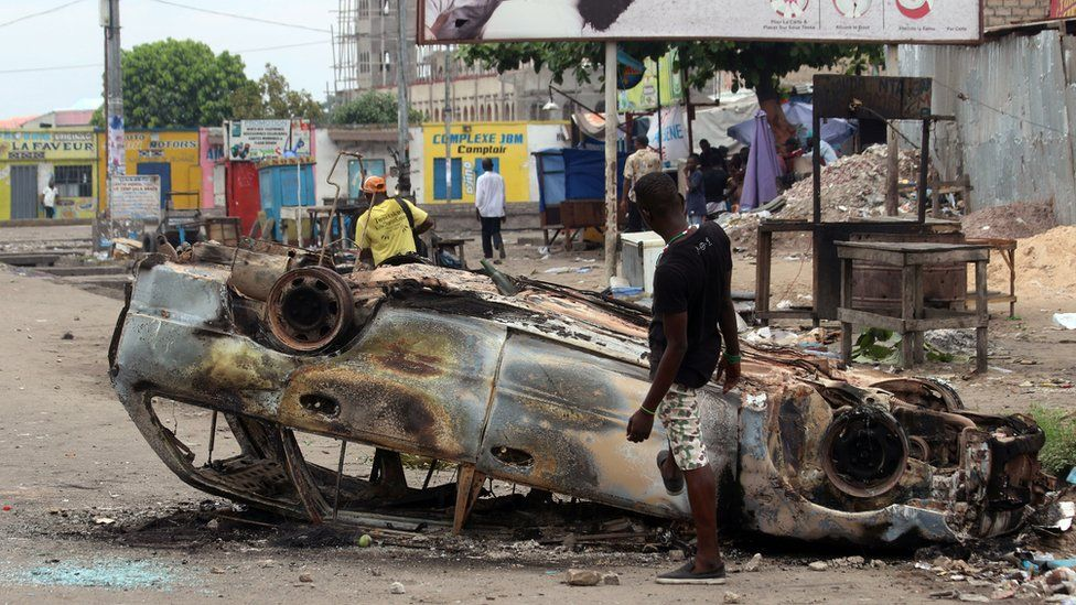 A man stands next to a burnt out car after a protest in Kinshasa, Democratic Republic of Congo, Monday, Sept. 19, 2016
