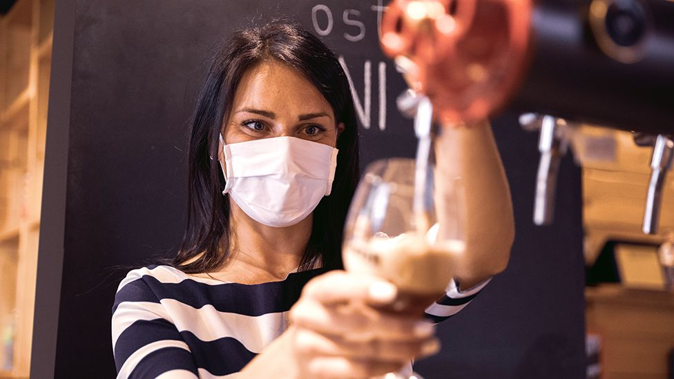 Barmaid with a mask pouring a drink