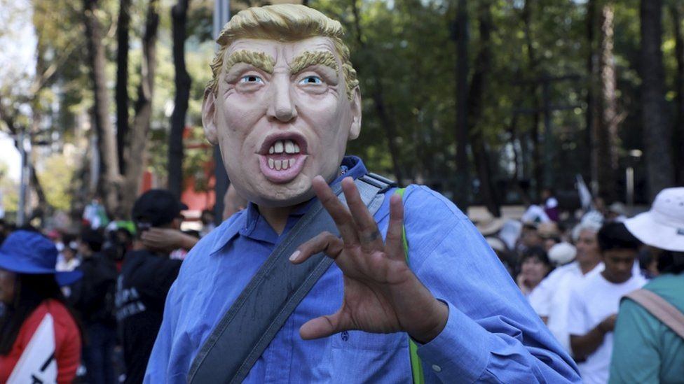 A man wears a mask depicting US President Donald Trump during a march demanding respect for Mexico and its migrants, 12 February 2017