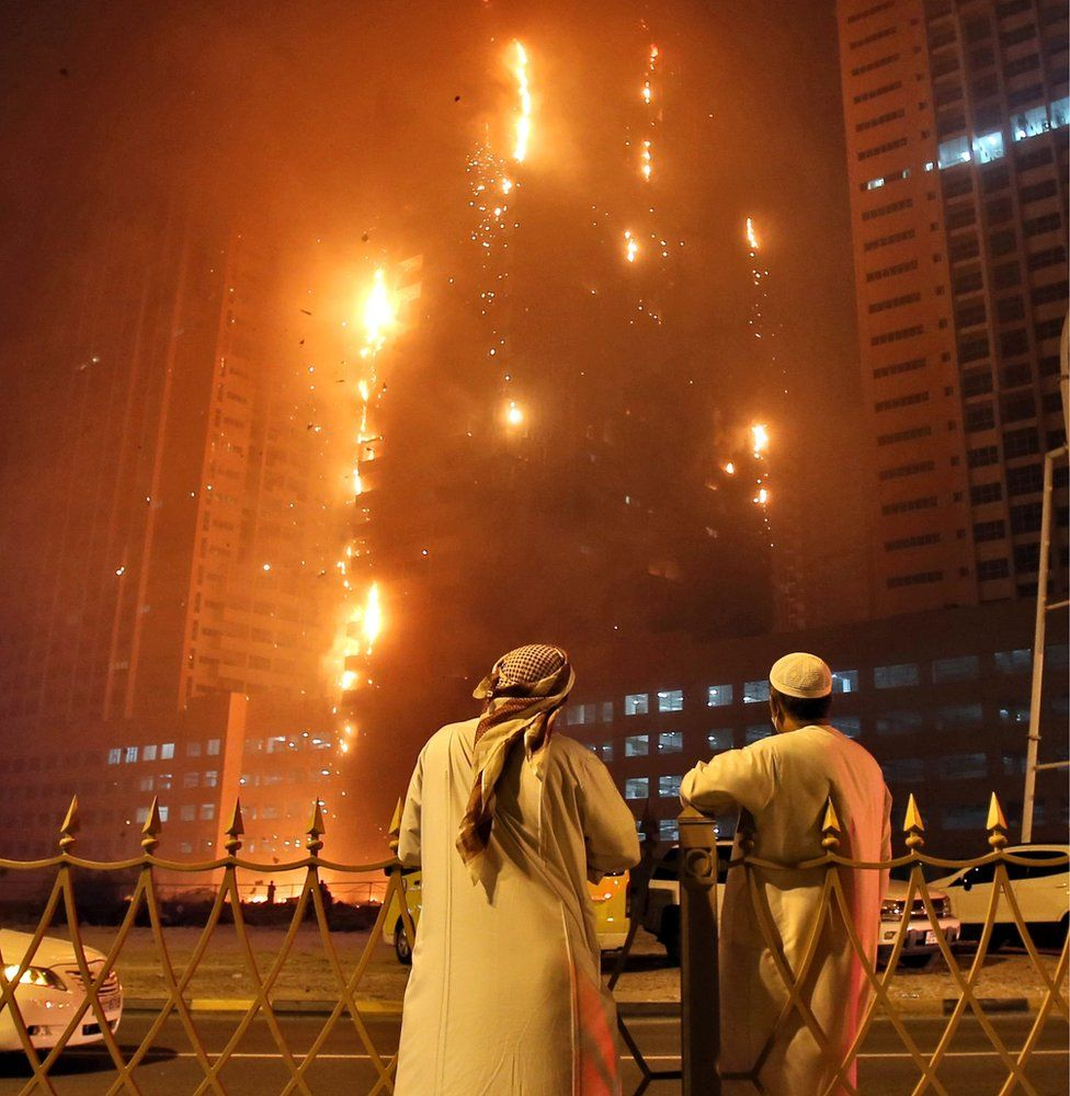 Two Emirati officials as a fire spreads up the side of the watch a high-rise building in Ajman, United Arab Emirates, early Tuesday, March 29, 2016
