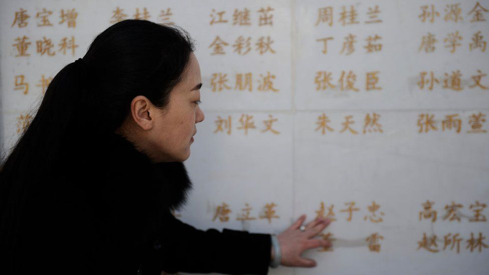 The wife of an organ donor touches her husband's name on a memorial for Chinese organ donors