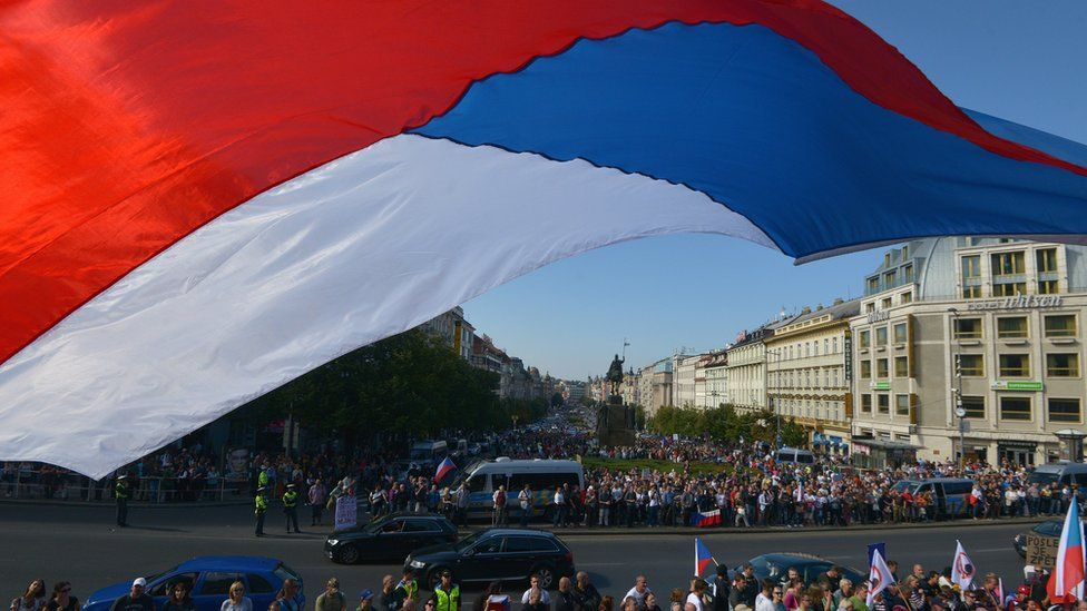 A Czech national flag flies over protesters attending an anti-migrants demonstration on September 12, 2015 in Prague.