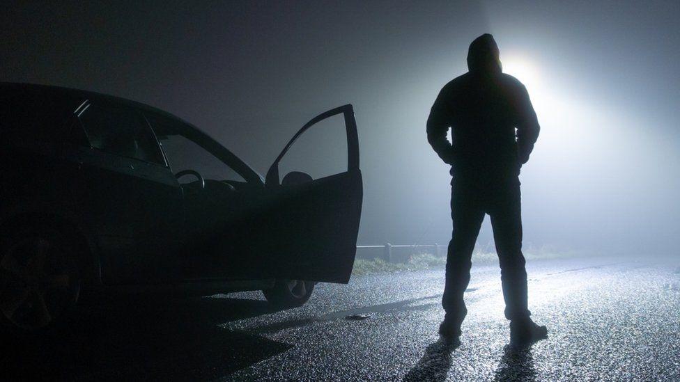 Shadowy man outside car
