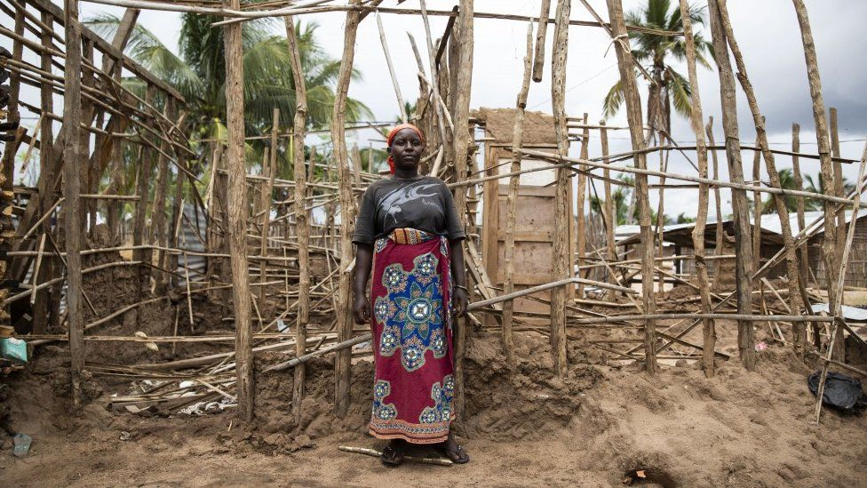 A lady who fled violence in northern Mozambique stands in front of her temporary house destroyed by Cyclone Kenneth