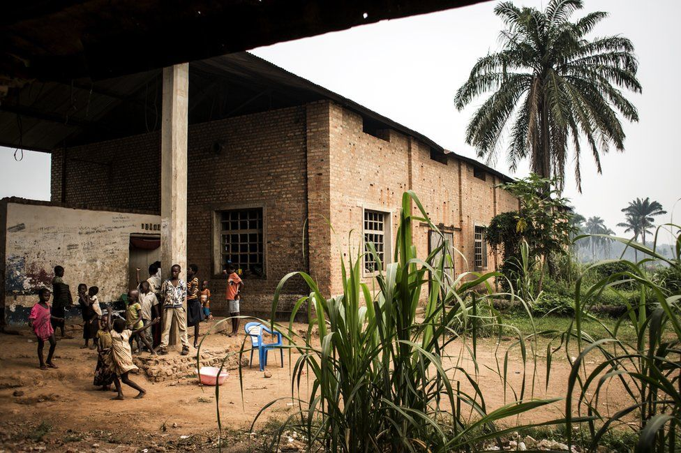 Displaced persons outside an abandoned warehouse, which is used by Internally Displaced Persons (IDPs) as a shelter from the ongoing conflict