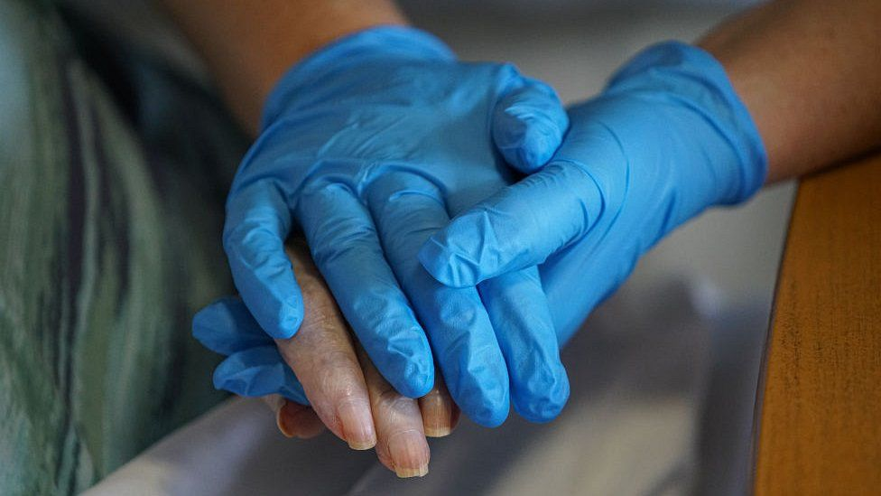 holding hands in plastic gloves