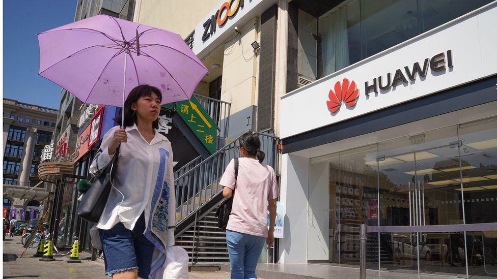 People walk past a Huawei store on July 1, 2019 in Dongdaqiao, Chaoyang District, Beijing.