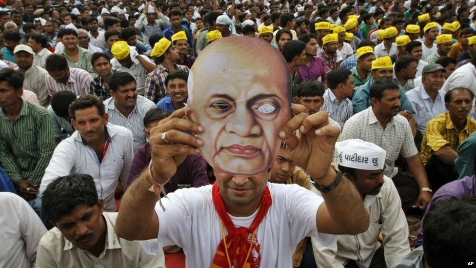 A Patidar or member of Patel community holds a mask of Indian freedom fighter and first Home Minister of Independent India Sardar Vallabhbhai Patel as he participates in a rally in Ahmadabad, India, Tuesday, Aug. 25, 2015.