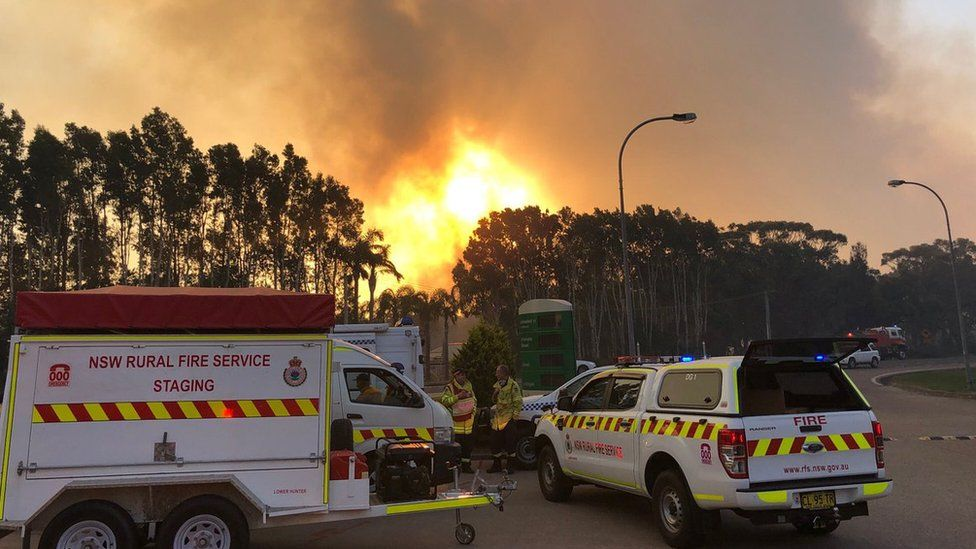 Fire crew vehicles in front of a bushfire at Port Stephens in New South Wales