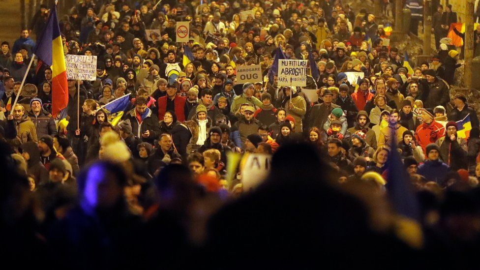 Demonstrators march in front of the government building during a protest in Bucharest, Romania, Saturday, Feb. 4, 2017
