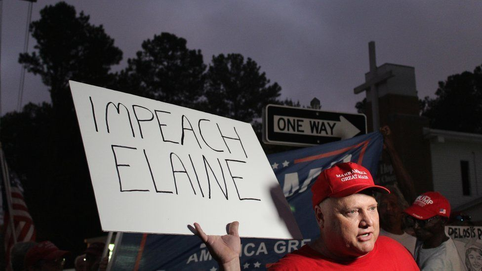"Trump supporter Richard Egger holding a sign saying ""Impeach Elaine"""