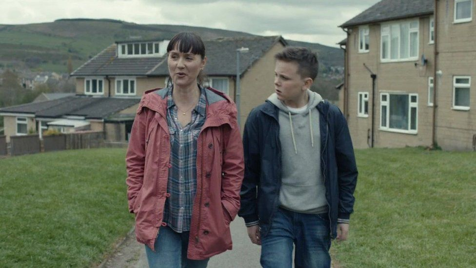 still from advert showing mother and son walking